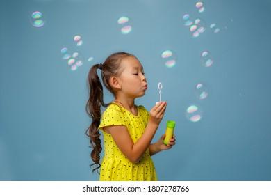 Asian girl Letn soap bubbles in the Studio on a blue background - Shutterstock ID 1807278766
