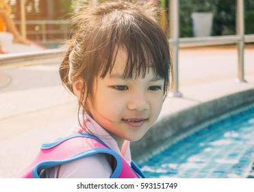 Asian girl with life jacket sitting on poolside