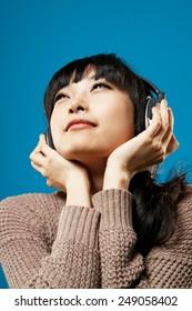 Asian girl listen music on studio blue background.