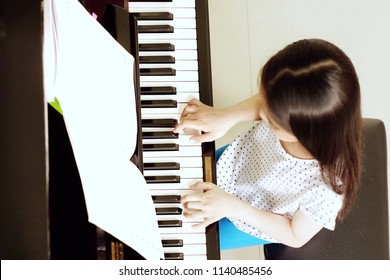 Asian girl long hair practicing piano.