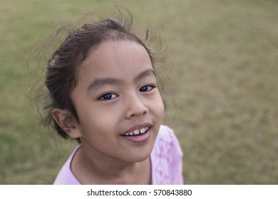 Asian girl look at camera and smiling in the park.
