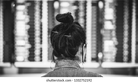 asian girl looking at flight schedule at airport terminal,black and white colot tone, single traveler concept