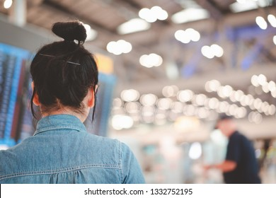 asian girl looking at flight schedule with blurred light bokeh of terminal background, single traveler concept