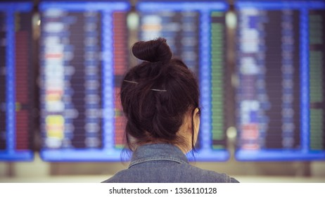 asian girl looking at flight schedule at airport terminal, single traveler concept