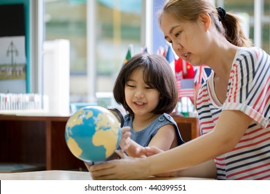 Asian girl looking at globe while listening to teacher with magnifying glass