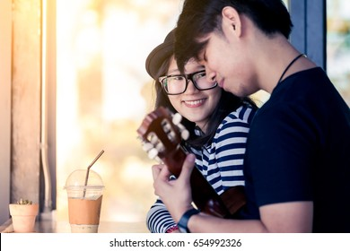 Asian girl looking at her boyfriend playing guitar with love in the cafe in vintage color tone