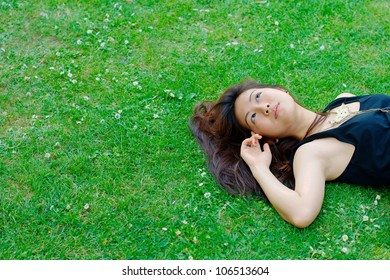 Asian girl lying on grass (with copy space)