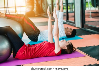 Asian girl and man exercises with a fitness ball in the fitness center with happiness.
