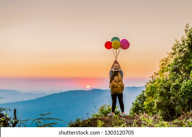 Asian girl with many colored balloons on the top of the mountain