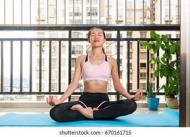 Asian girl meditating at the balcony. Home workout