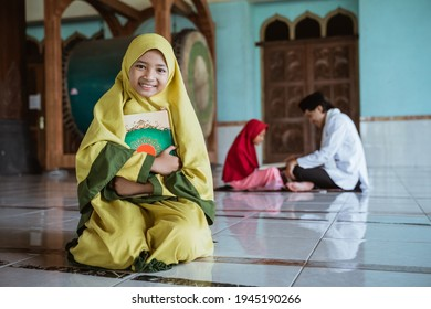 asian girl muslim smiling holding al quran book and learning to read quran with muslim teacher aur ustad