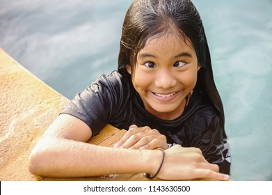 Asian girl on the edge of the swimming pool pretend to strabismus