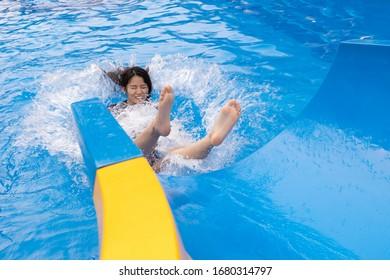 Asian girl on water slide at aquapark. Summer holiday.