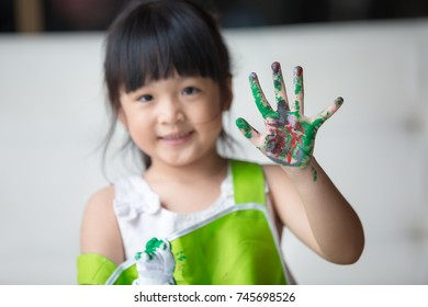 Asian girl painted on plaster doll with Stained hands