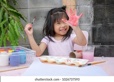 Asian girl painting on her hand. Painting is play therapy for ADHD kids (Attention deficit hyperactivity disorder),can be used to address emotional problems. Happy concept.