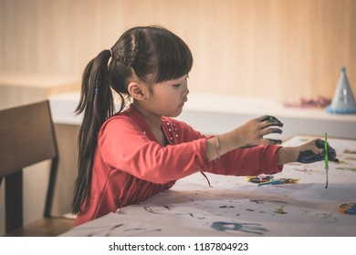 Asian girl is painting on paper in Art group