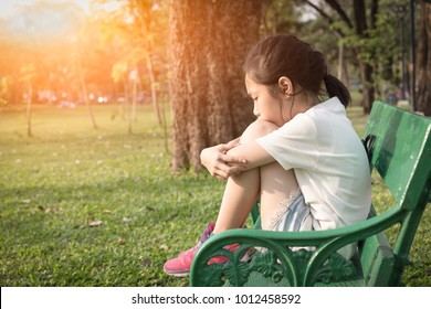 Asian girl in the park,depressed sitting on the bench,sorrow,unhappy,