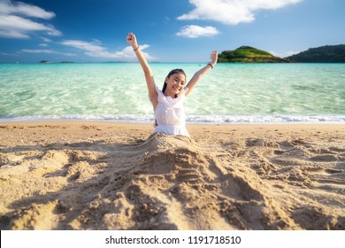 Asian girl play with sand on the beach and island background, this immage can use for travel, relax and summer concept