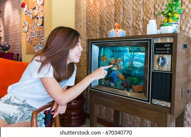 an Asian girl is playing with the goldfish in the tv fish tank, strange furniture