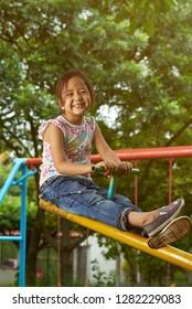 Asian girl playing on a see-saw at park. Filipina kid
