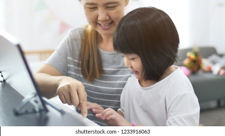 Asian girl playing piano with her mother
