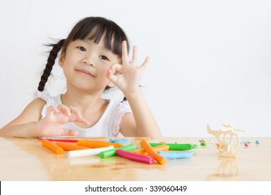Asian girl playing plasticine.