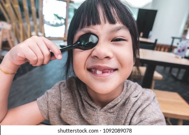 Asian girl is playing with spoon on dinner table