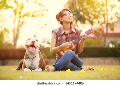 Asian girl playing ukulele  with dog in the park