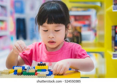 Asian girl plays with colorful plastic toy blocks