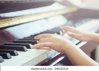 Asian girl plays piano with warm light