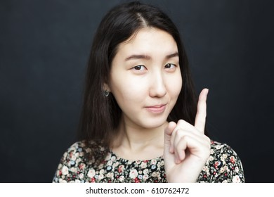Asian girl points with finger up. Give advice or recommendation