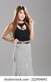 Asian girl posing in Hollow Out Black Sleeveless Tank Tops with long slim black and white striped skirt with red hat.