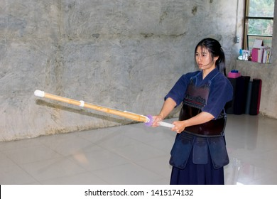 Asian girl practice Kendo sport by using Shinai sword swinging and hitting, she wears armors Bogu equipment as protection of her chest and hip. (Japanese old martial art)