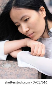Asian girl in profile laying on her hands