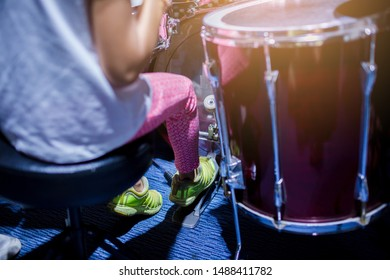 Asian girl put yellow sport shoes and playing the drum set and bass drum with foot in music room , the concept of musical instrument.