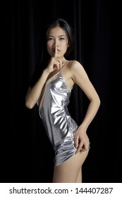 Asian girl quiet gesture in silver dress against black background