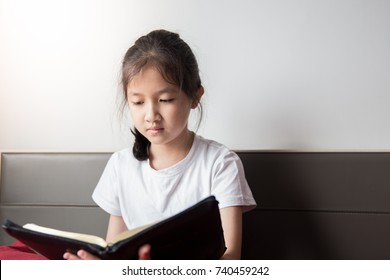 Asian girl read holy bible in the morning after wake up from sleep and put her hand on red pillow for comfortable hand because holy bible so big and heavy  than her hand. Concept kids read holy bible.