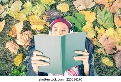 asian girl reading book in a garden . leafs are on the ground and surround her. autumn concept