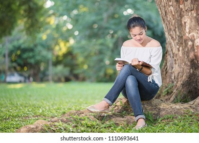 Asian girl reading book at park in summer. Woman Read concept.