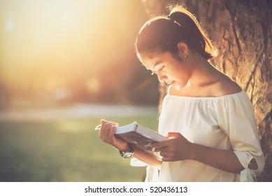 Asian girl reading book at park in summer sunset light.
