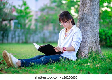 asian girl reading book under tree in public park