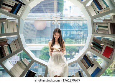 Asian girl reading on a bookshelf in a library in her university