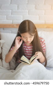 Asian girl reading story book on the bed