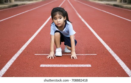 asian girl ready to start running game on the line of outdoor arena