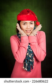 Asian girl with red christmas hat excited and smile on dark green background