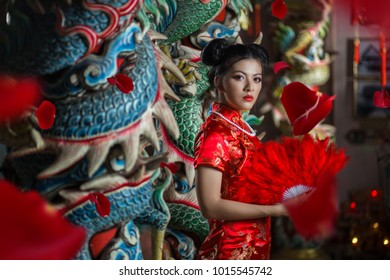 Asian girl in red dress standing in holy place on Chinese New Year.