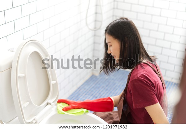 Asian girl with red rubber gloves is cleaning toilet bowl by using toilet wipe. She is sitting and smiling while cleaning the bathroom. Seen in top side view. Happy toilet cleaning concept.