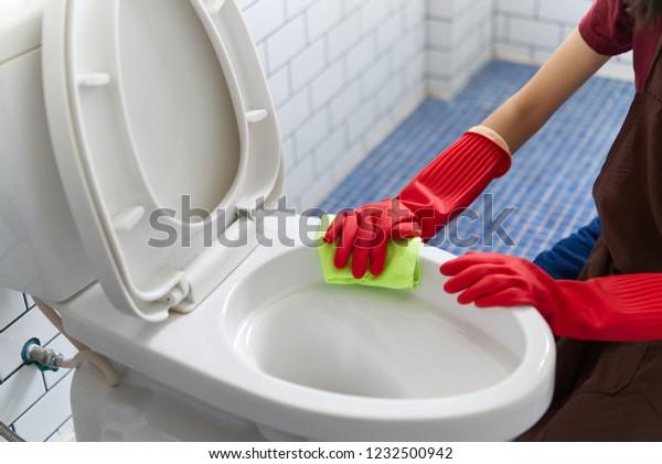 Una chica asiática con guantes de goma rojos está limpiando el tazón del baño usando un limpiaparabrisas. Ella está sentada y limpiando el baño. Vista en la parte superior. Contento concepto de limpieza de baños.
