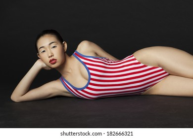 Asian girl in Red White Blue Swimsuit laying on Black Background