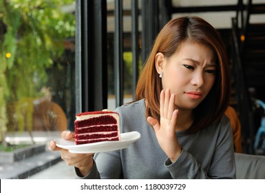 Asian girl refuses cake because she is controlling her calories,Dieting,Cake is heigh calories for dieting women,Women don't like cake